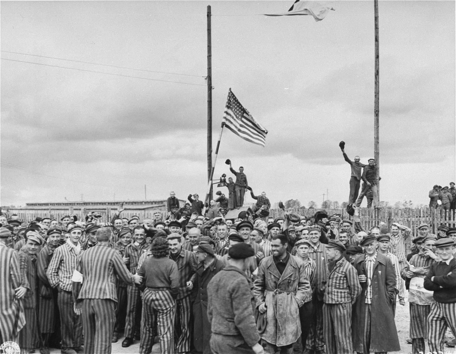 Inmates waving a home-made American flag greet U.S. Seventh Army troops upon their arrival at the Allach concentration camp.