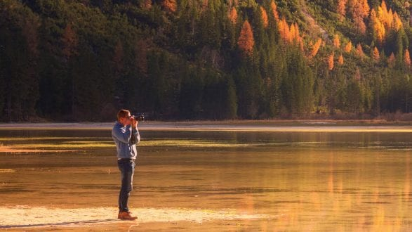 A photographer on the shore of a lake surrounded by mountains festooned in autumn colors.