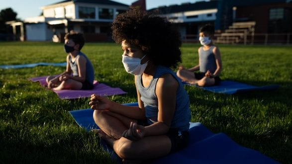 Group of kids wearing face masks performing yoga in the garden