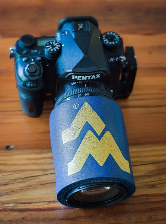 A West Virginia Mountaineers beer cozy around a lens to hold hand warmers in place. For many lens, you might need to cut this and either apply Velcro strips to close it back up, tape it with gaffer's tape, or tie rubber bands around it.