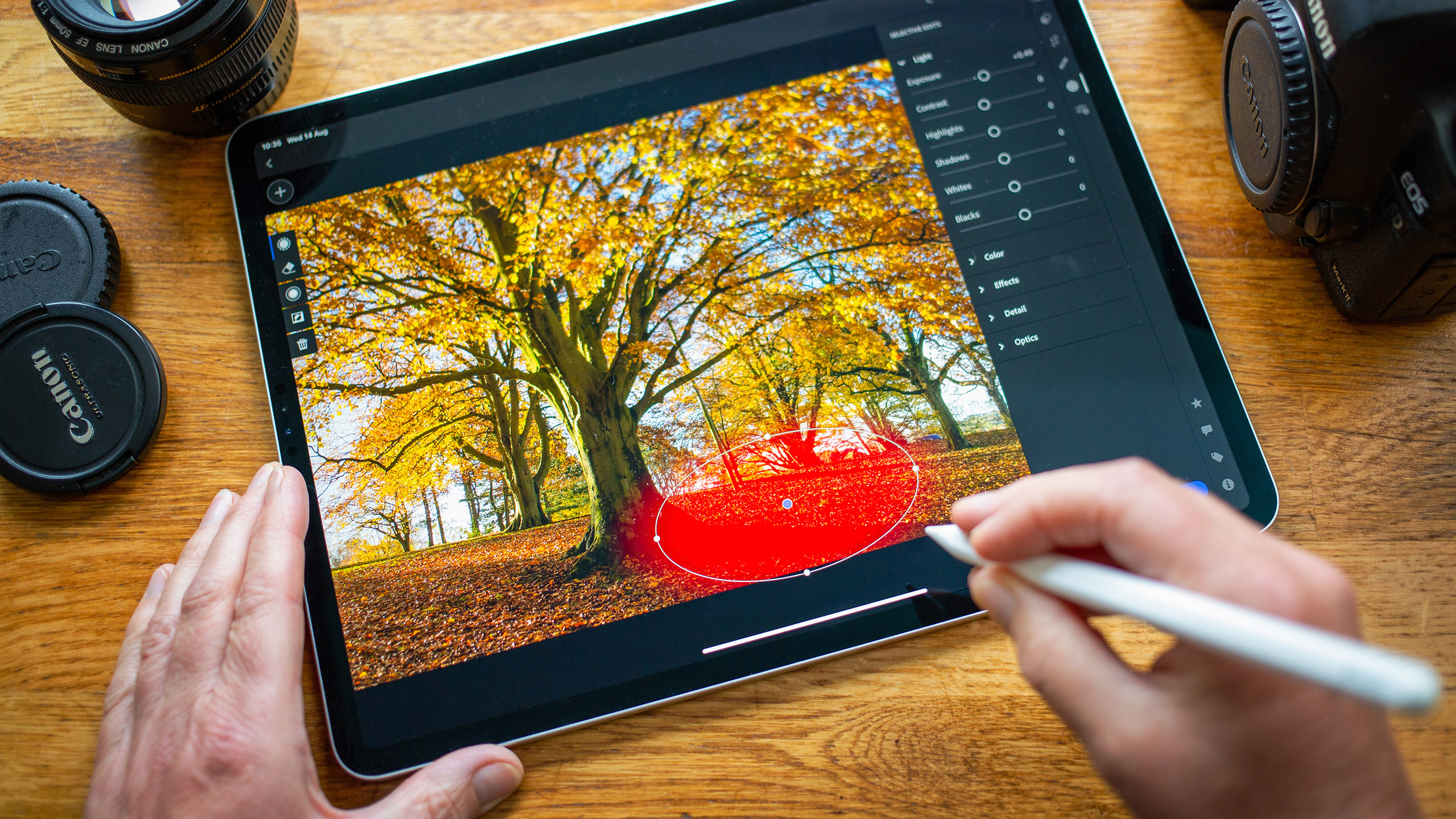 BATH, UNITED KINGDOM - AUGUST 14, 2019 : Close up of someone using an iPad Pro running the Adobe Lightroom App to make selective adjustment to a photograph of colourful trees.
